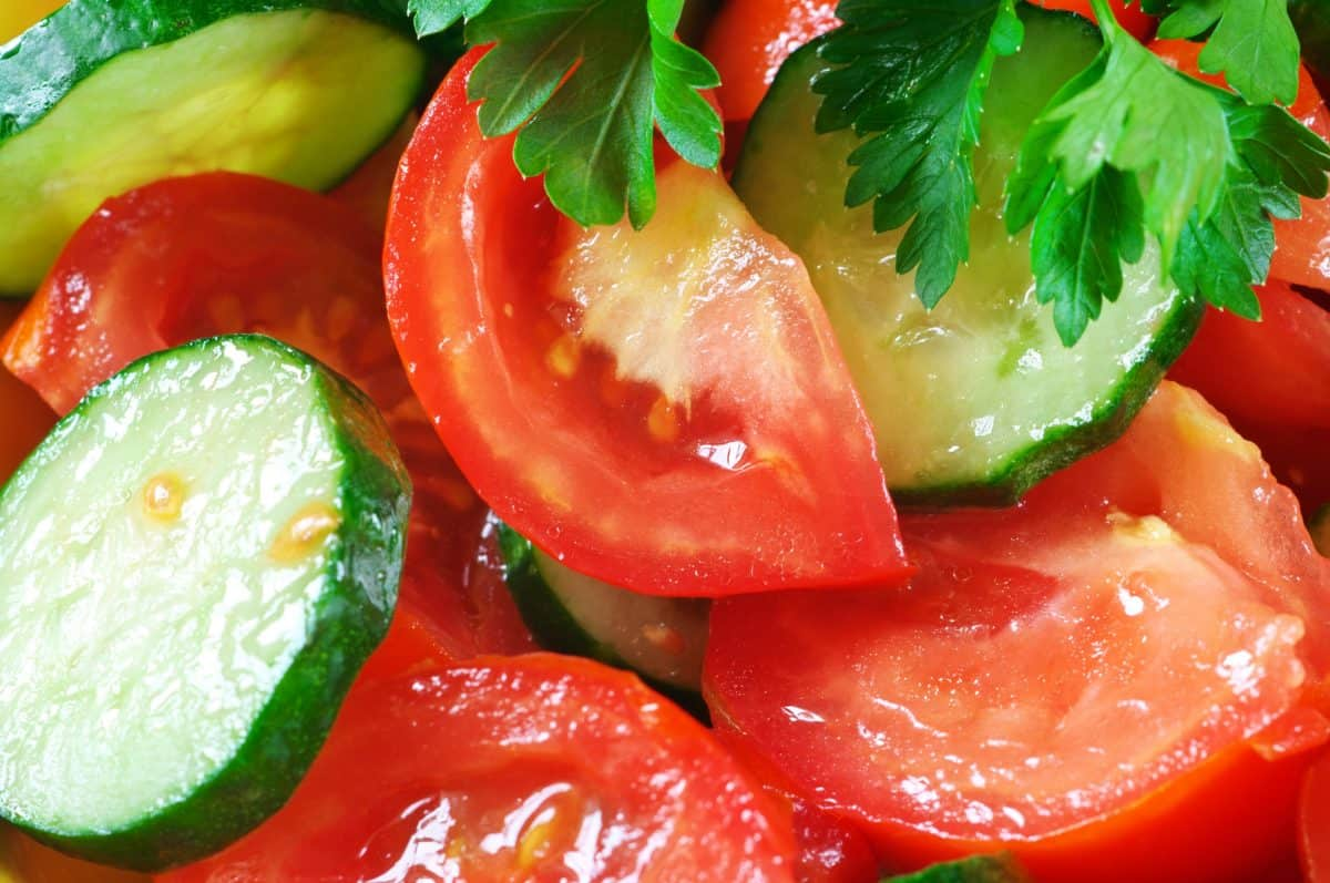 9569353 - close-up of fresh salad of tomatoes, cucumbers and parsley. full frame.